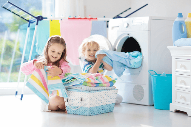 Kids holen die frische Wäsche aus der Waschmaschine