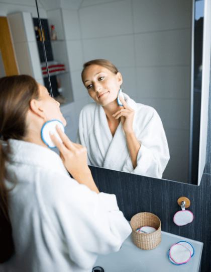 Frau schminkt sich mit blauem Abschminkpad ab